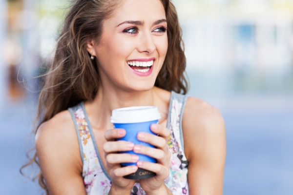 woman smiling and holdign a cup of coffee after her cosmetic dentistry procedure