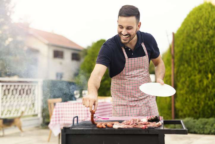 Young man in an apron grilling sausages.