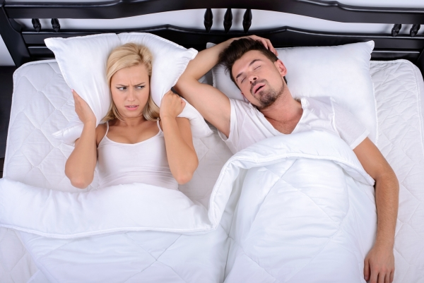 man suffering from sleep apnea keeps bed partner awake